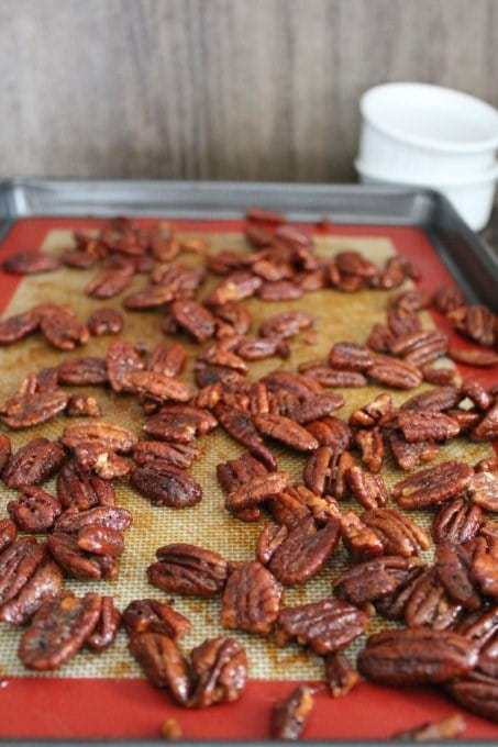 Browned candied pecans on a cookie sheet.