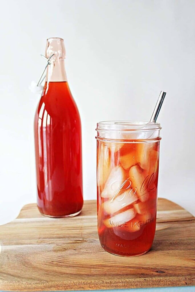 A tall bottle filled with bright red strawberry iced tea with a bail style lid sits on top a wooden cutting board. In the foreground, a tall wide mouth mason jar filled with opaque white ice and some of the bright red strawberry iced tea. There is a stainless steel straw in the mason jar