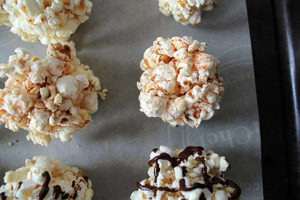 Sugar free popcorn balls on a parchment paper lined cookie sheet. Some are sprinkled with cinnamon, some are drizzled with melted chocolate.