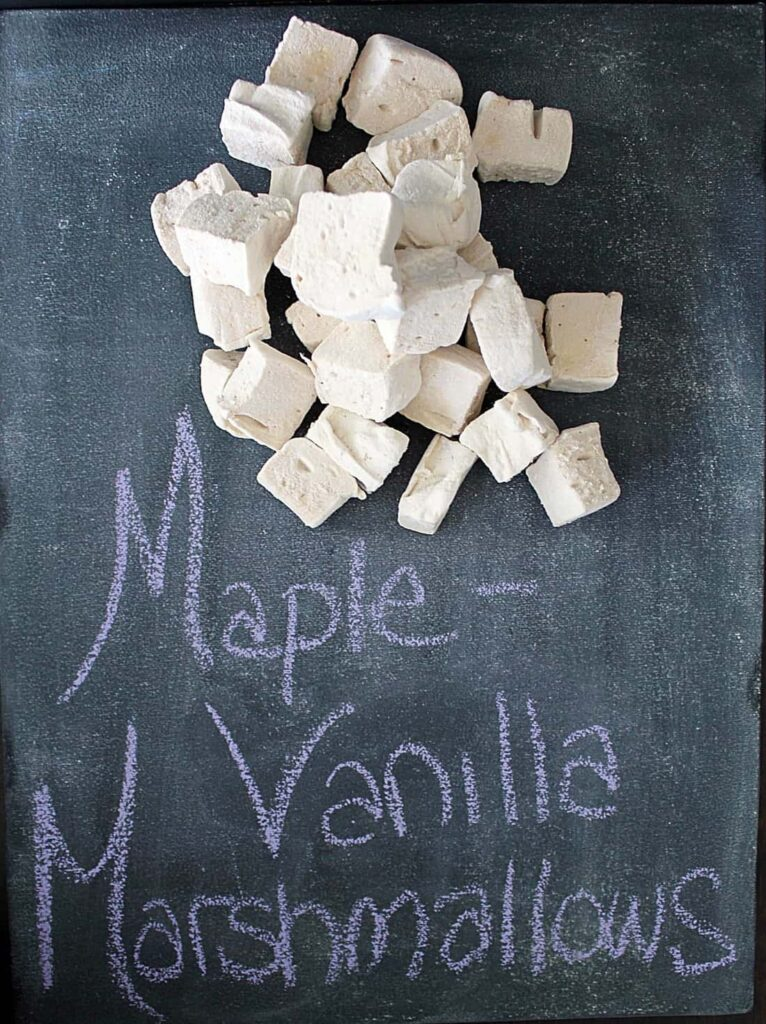 a pile of cube shaped marshmallows on the top half of a chalky, worn chalkboard with the words Maple - Vanilla Marshmallows written in purple chalk beneath