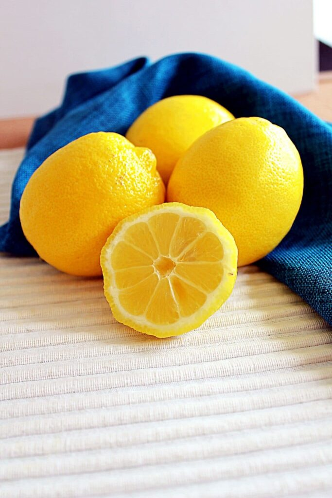 An overhead look at a bright turquoise napkin made of a crosshatched fabric is gathered with 3 whole shiny, bright yellow lemons on top. Near the bottom of the photo there is a cross section of a lemon, where you can see the vivid yellow rind surrounding the white pith, and the triangular segments of the lemon