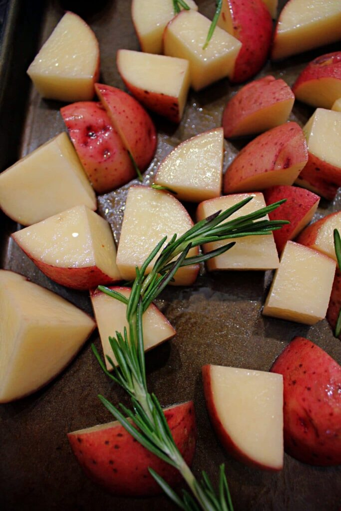 red skinned potatoes, coarsely shopped, glistening from being coated in oil, laying atop a dark baking sheet that has been stained a brownish colour from years of use. On top of the potatoes is a bright green sprig of rosemary