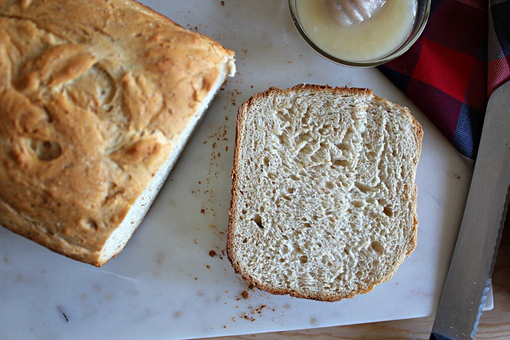 A slice of honey whole wheat bread laying in front of the loaf it was cut from. The crust is golden brown and the crumb is flecked with wheat germ and air pockets.