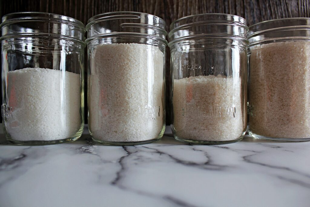 a sidewise view of 4 different jars of smoked salt. From left to right, they increase in smoky colour.