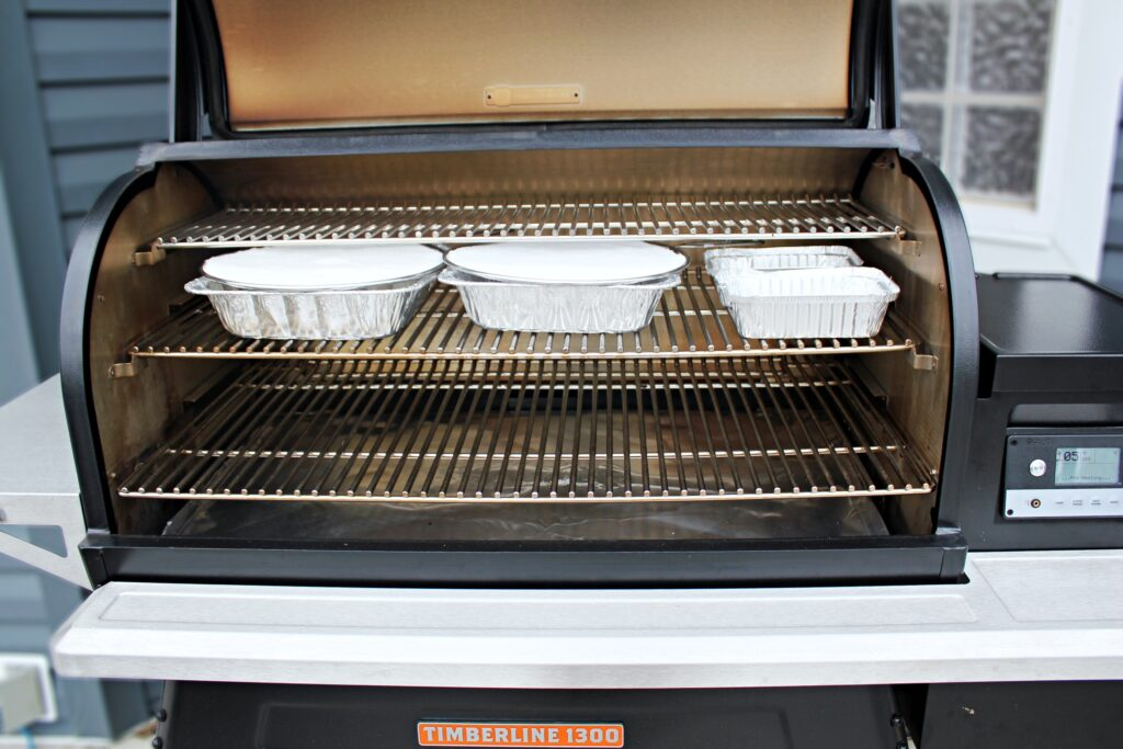a traeger timeberline 1300 with the lid open filled up with aluminum pans ready to smoke salt.