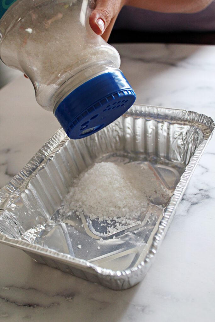 a child's hand pouring sea salt into an aluminum pan.