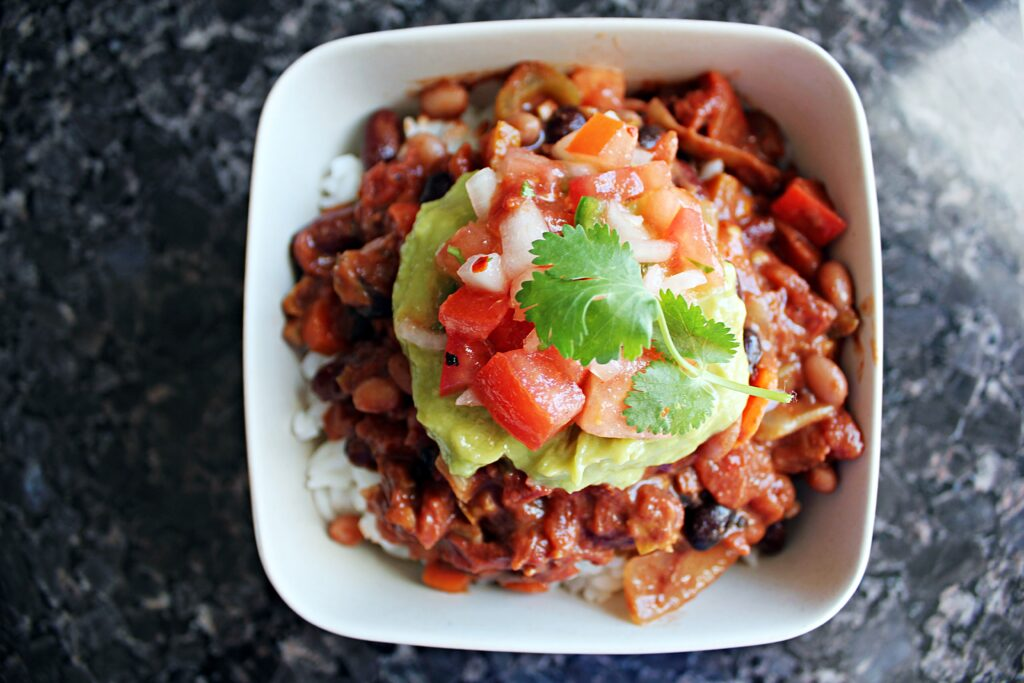 overhead view of a white bowl. Chili is piled high, then topped with green guacamole, red pico de gallo and a fresh cilantro leaf.