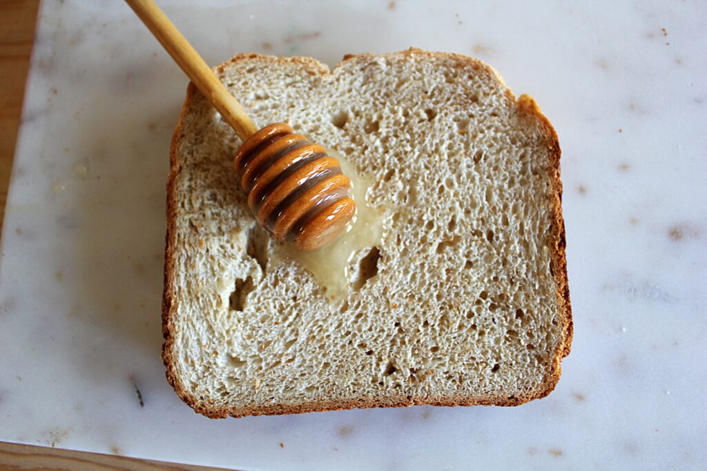 A honey dipper resting atop a slice of honey whole wheat bread.