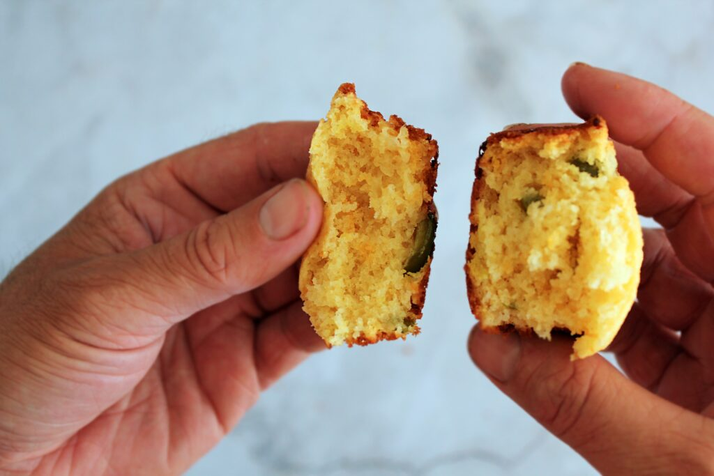A mans hands cracking open a jalapeno cornbread muffin. You can see the green jalapenos and slightly orange cheddar cheese.