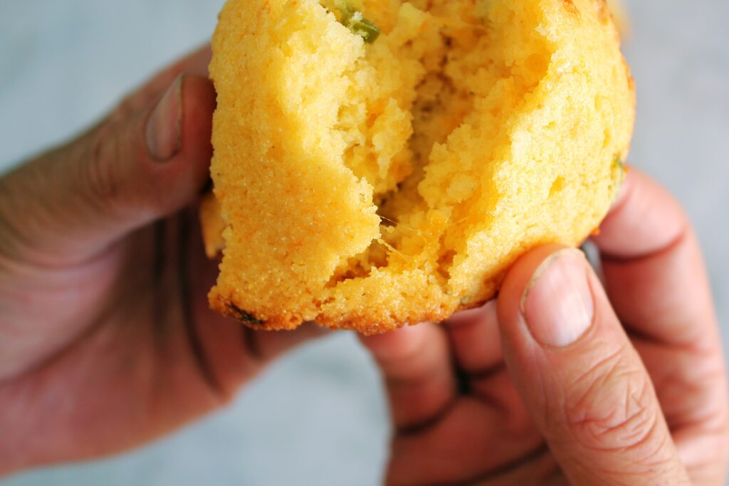 A mans hands holding a jalapeno cheddar cornbread muffin and tearing it in half. You can see visible strings from the melted cheese.