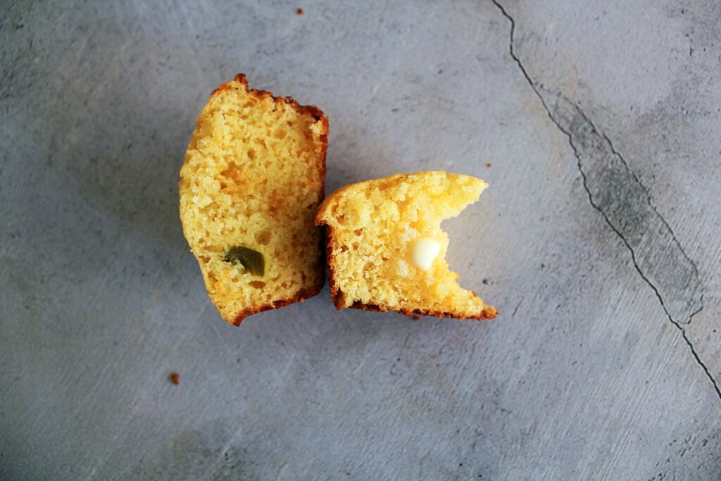 A jalapeno cornbread muffin cut in half with melting butter on one half and a bite missing.
