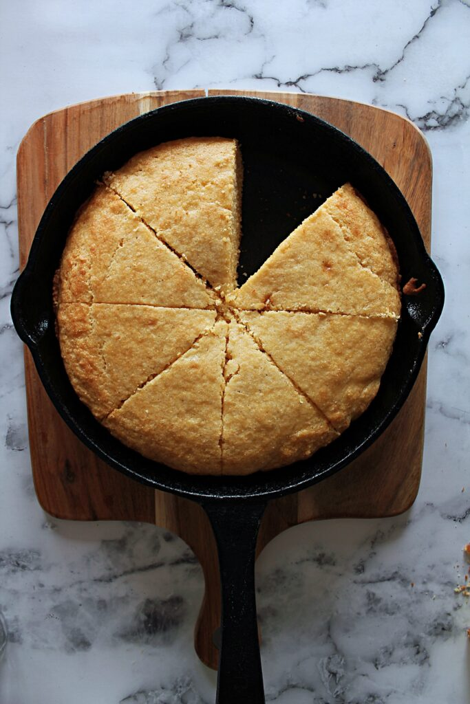 a black cast iron skillet holding 7 wedges of cornbread. One is missing.