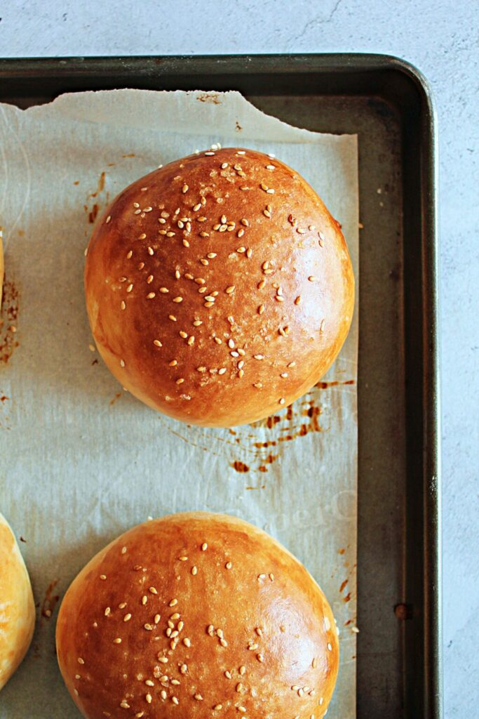 Close up of the homemade hamburger buns, they are golden brown with sesame seeds and sea salt sprinkled on top.