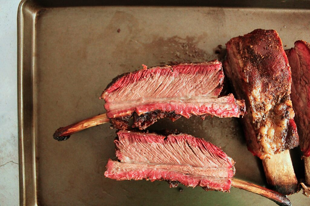 Two smoked chuck ribs laying on their cut side, showing a bright red smoke ring and the tender beef flesh.