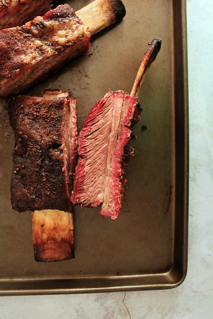 Two ribs side by side on a baking sheet, one is bone side down showing the smoked bark and the other is cut side up showing the smoke ring and tender beef meat.