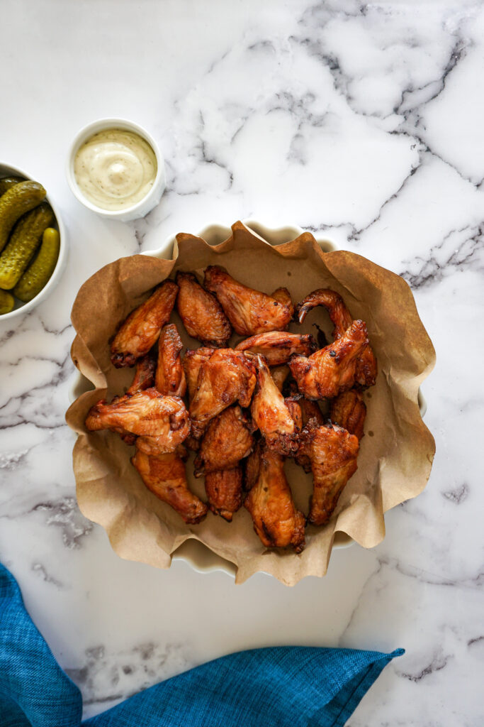 Traeger smoked chicken wings in a brown paper lined white bowl.