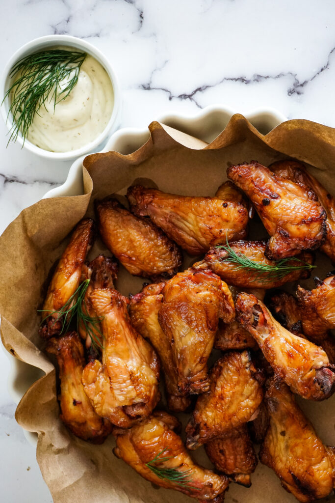 Smoked dill pickle chicken wings in a white bowl with a dill mayo dip.