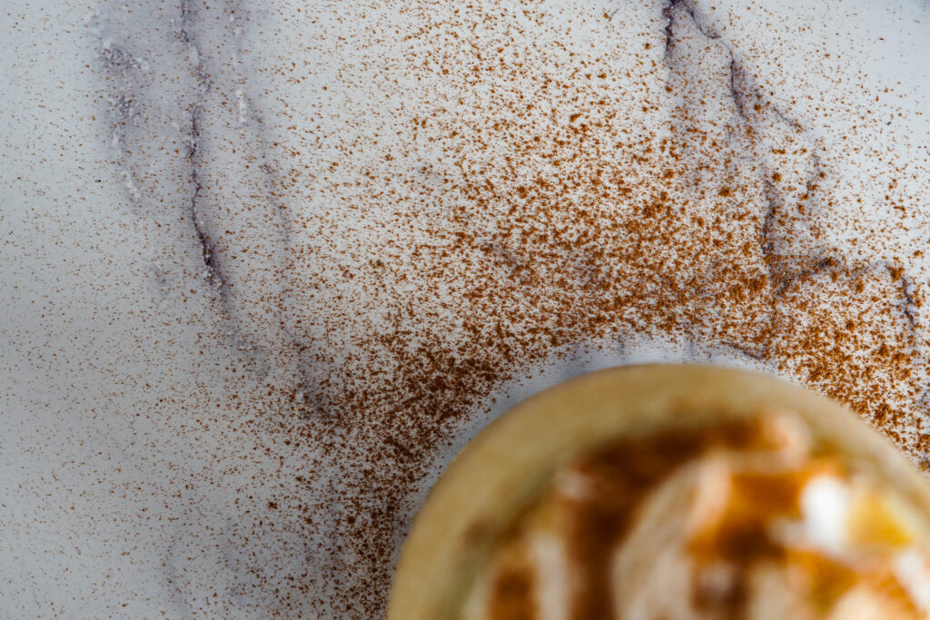 A close up of the cinnamon that was sprinkled on top of the whipped cream topped pumpkin pie milkshake.