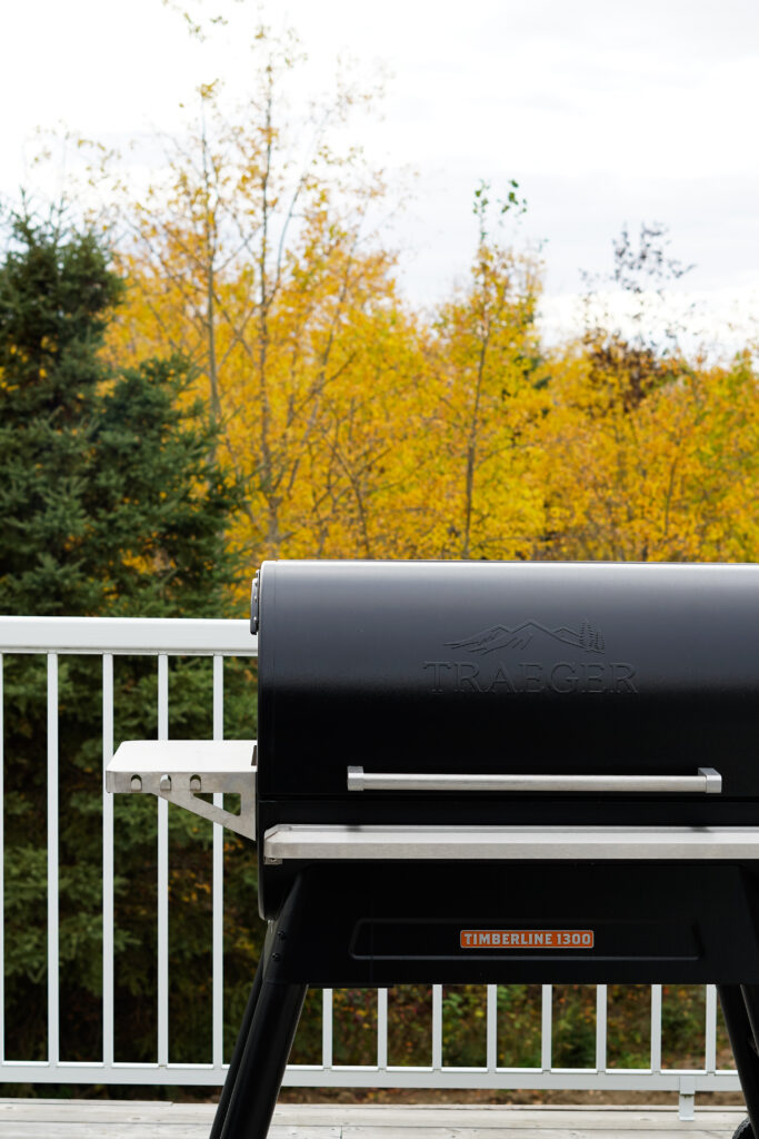 A Traeger Timberline smoker set against a background of colour changed fall leaves.