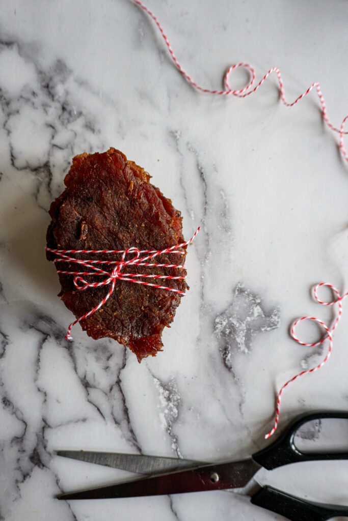 A stack of beef jerky tied up in red and white butcher's twine.